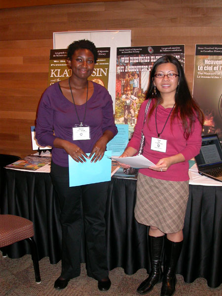 Meleisa Ono-George (left), a research assistant for the Mysteries Project, with a visitor at the display